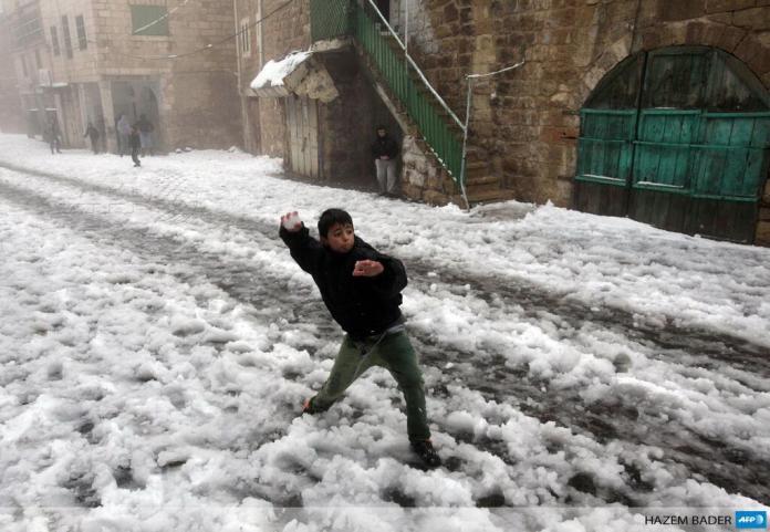 Hebron imbiancata: un ragazzino palestinese gioca con le palle di neve insieme ai suoi amici nei pressi della moschea di Ibrahimi conosciuta anche come la Tomba dei patriarchi (foto Bader/Afp)
