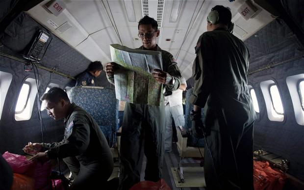 Izam Fareq Hassan (al centro), capitano dell'Aeronautica militare della Malesia, consulta le mappe durante le operazioni di ricerca e soccorso (foto Afp)