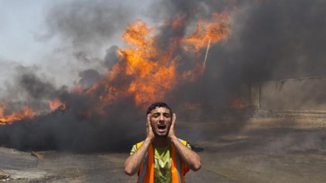 Un vigile del fuoco di Gaza City vicino alle fiamme in un deposito delle Nazioni Unite dopo l'attacco israeliano (foto Mahmud Hams/Afp)